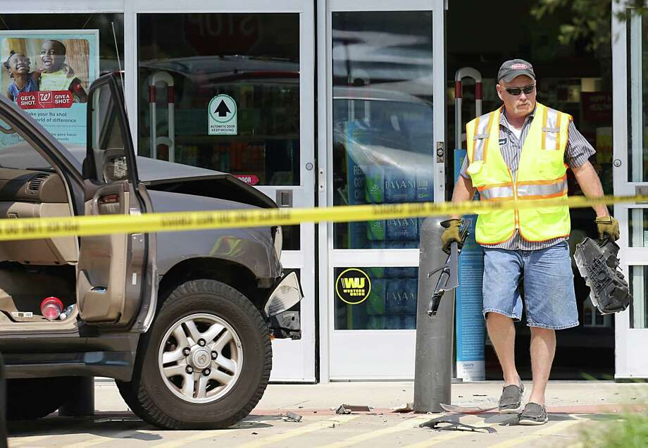 A tow truck driver picks up broken pieces of the subject's car at a Walgreens drug store in Kemah. Photo: Thomas B. Shea, Freelance / © 2015 Thomas B. Shea