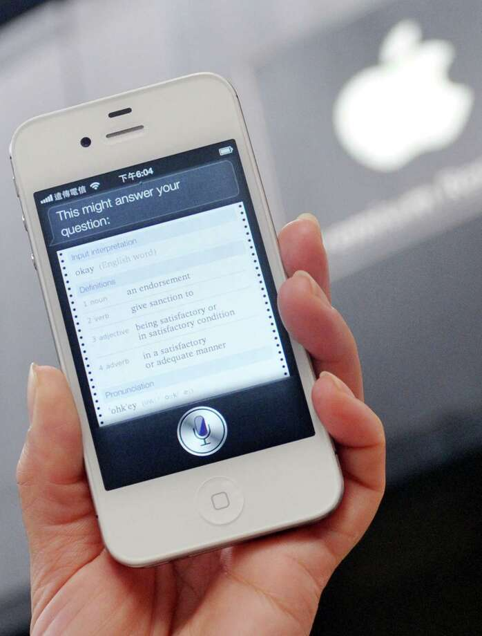 A woman displays Siri, the voice-activated assistant technology, on an Apple iPhone. Siri may get more to do as iPhones and iPads receive new software. Photo: MANDY CHENG, Stringer / AFP