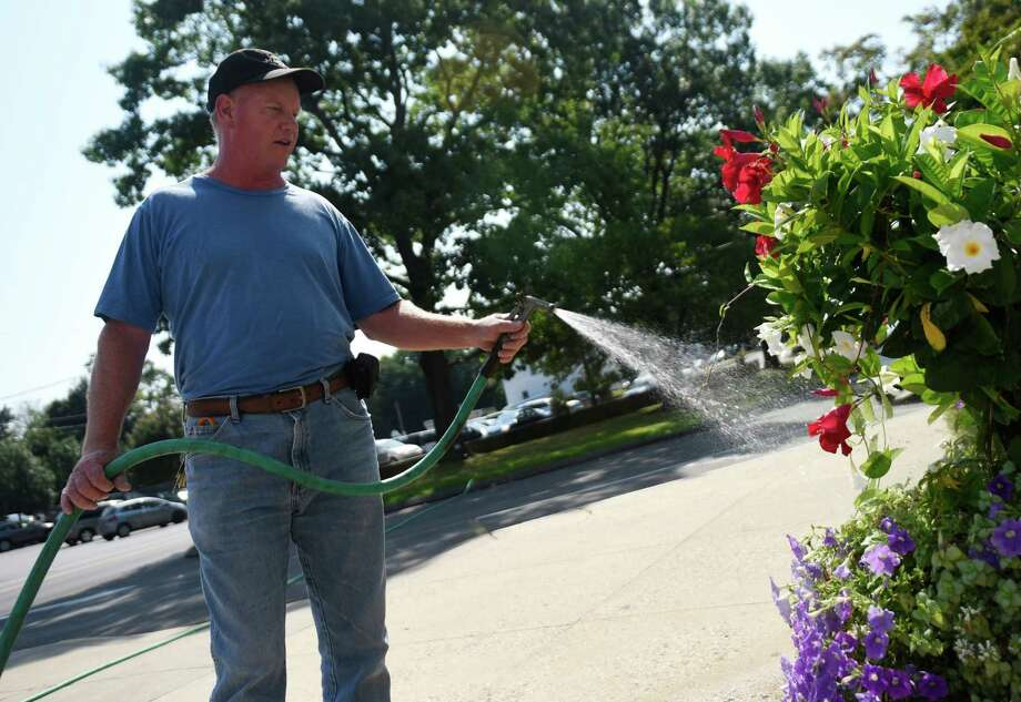Steve Coffey, who is in charge of maintenance at St. Catherine of Siena Church, waters the potted plants in front of the church in the Riverside section of Greenwich, Conn. Tuesday, Sept. 8, 2015. Tuesday's high temperature reached the mid-90s, but temperatures are expected to dip to the upper-80s Wednesday with a chance of an evening thunderstorm. Photo: Tyler Sizemore / Hearst Connecticut Media / Greenwich Time