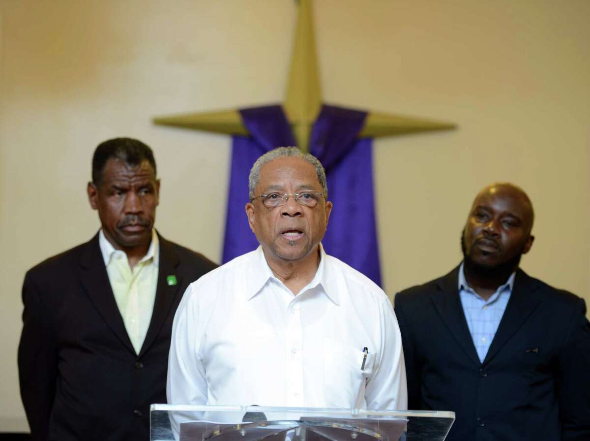 Bishop John White, senior pastor of Cathedral of Praise, speaks during a press conference Tuesday, Sept. 8, 2015, at Shiloh Baptist Church in Bridgeport, Conn. The Rev. Carl McCluster, left, William Marshall, right, and other clergy and citizens gathered to voice their questions about mayoral candidate Joe Ganim's participation in a legal case involving a Klu Klux Klan member.