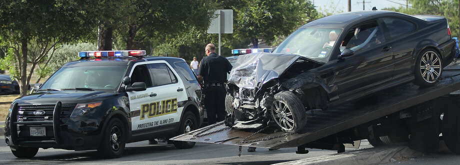 A BMW sedan is loaded onto a wrecker after its driver was rammed, causing it to crash into another vehicle and an 18-wheeler at Rogers and Culebra roads. Photo: John Davenport /San Antonio Express-News / ©San Antonio Express-News/John Davenport