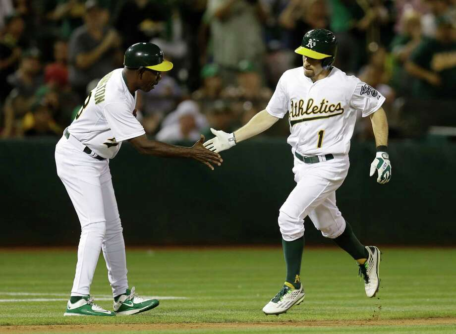 Oakland Athletics' Billy Burns, right, is congratulated by third base coach Ron Washington after hitting a home run off Houston Astros' Scott Kazmir during the third inning of a baseball game Tuesday, Sept. 8, 2015, in Oakland, Calif. (AP Photo/Ben Margot) Photo: Ben Margot, STF / AP