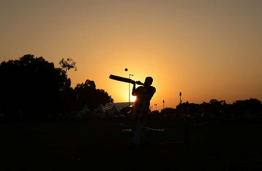 An Indian man hits a shot as he plays cricket with others near the India Gate monument in New Delhi on September 8, 2015.  Photo: Money Sharma, AFP / Getty Images