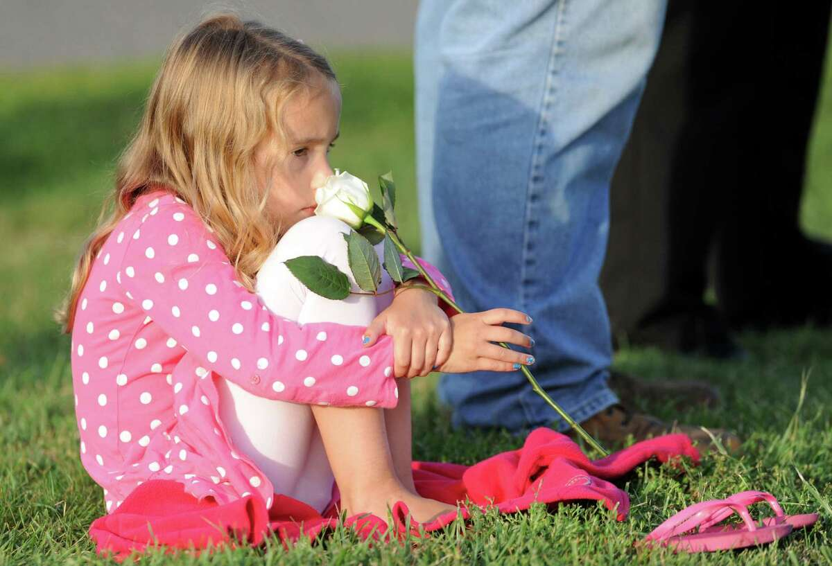 Six-year-old Lainey Grumet, of Monroe, pays tribute to her uncle Derek Statkevicus by attending Connecticut's annual 9/11 ceremony at Sherwood Island State Park in Westport, Conn., Wednesday, Sept. 10, 2014.