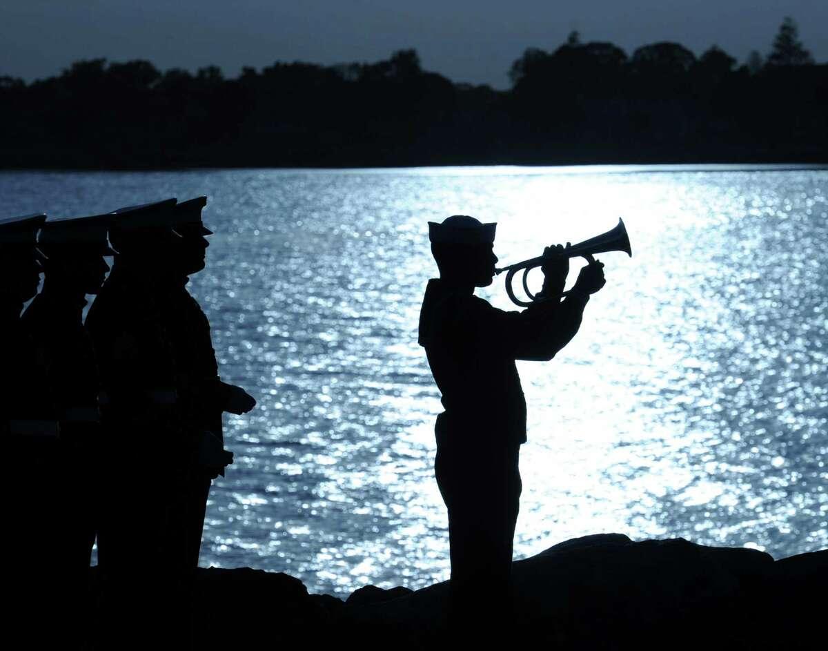 U.S. Navy bugler Milton Villa of North Bergen, N.J., plays