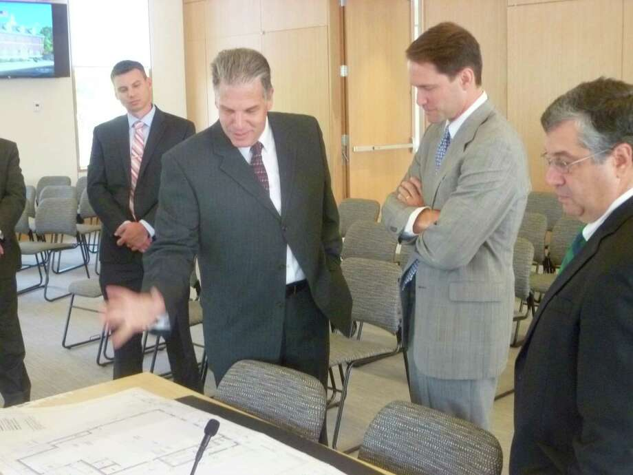 Second from left, Richard Carratu, the developer of a permanent New Canaan post office displays floor plans for U.S. Rep. Jim Himes-D-4, and New Canaan First Selectman Rob Mallozzi.  Carratu said he hopes to have the new Federal style building with brick cupola finished and open within the year. Photo: Martin Cassidy / Hearst Connecticut Media / New Canaan News