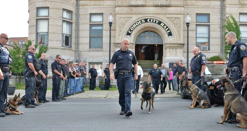 Officer and K-9 handler Sean McKown, center, walks K-9 Jeter out of the Cohoes Police Station on his final day of work Wednesday Sept. 9, 2015 in Cohoes, NY. (John Carl D'Annibale / Times Union)
