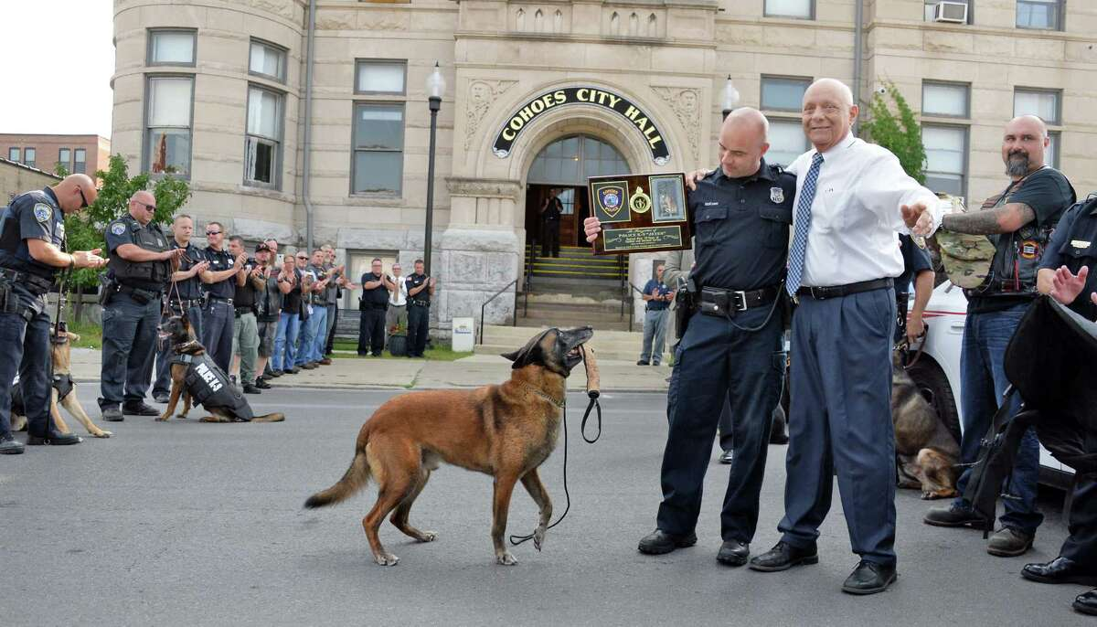 Officer and K-9 handler Sean McKown, center, and retiring K-9 Jeter receive a plaque from Cohoes Mayor George Primeau outside Cohoes Police Station Wednesday Sept. 9, 2015 in Cohoes, NY. (John Carl D'Annibale / Times Union)