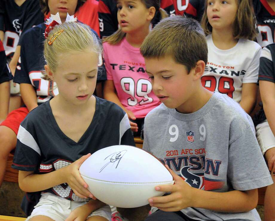 Emma Kimmel admires her brother's, Nathan, J.J. Watt autographed football during the J.J. Watt Day at Galatas Elementary School. The school was hoping to get at least 99 students and teachers wearing a Watt jersey, they exceeded that number. Photograph by David Hopper. Photo: David Hopper, For The Chronicle / freelance