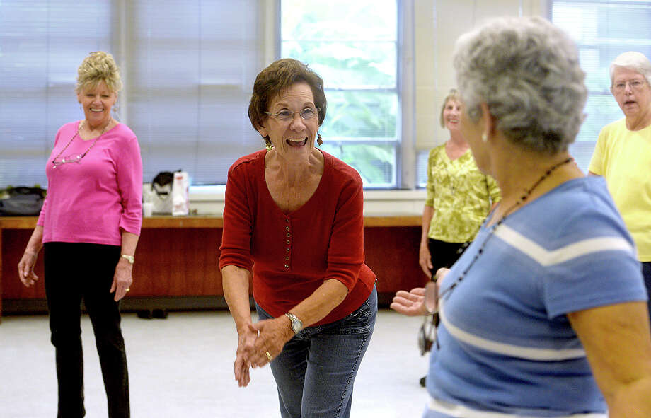 Kay Jordan (center) jokes with Jeri Speyrer after finishing a number as they and members of the dance troupe The Boot Scooters rehearse for an upcoming performance at The Meadows nursing home in Orange during their Tuesday afternoon meeting at the Best Years Senior Center in Beaumont. The group originated 20 years ago, and the current 9-member team performs at venues and events throughout the area several times each month. They also hold line dancing classes for seniors at the center every Tuesday afternoon, with new members always welcome.  Photo taken Tuesday, September 8, 2015  Photo by Kim Brent Photo: Kim Brent / Beaumont Enterprise