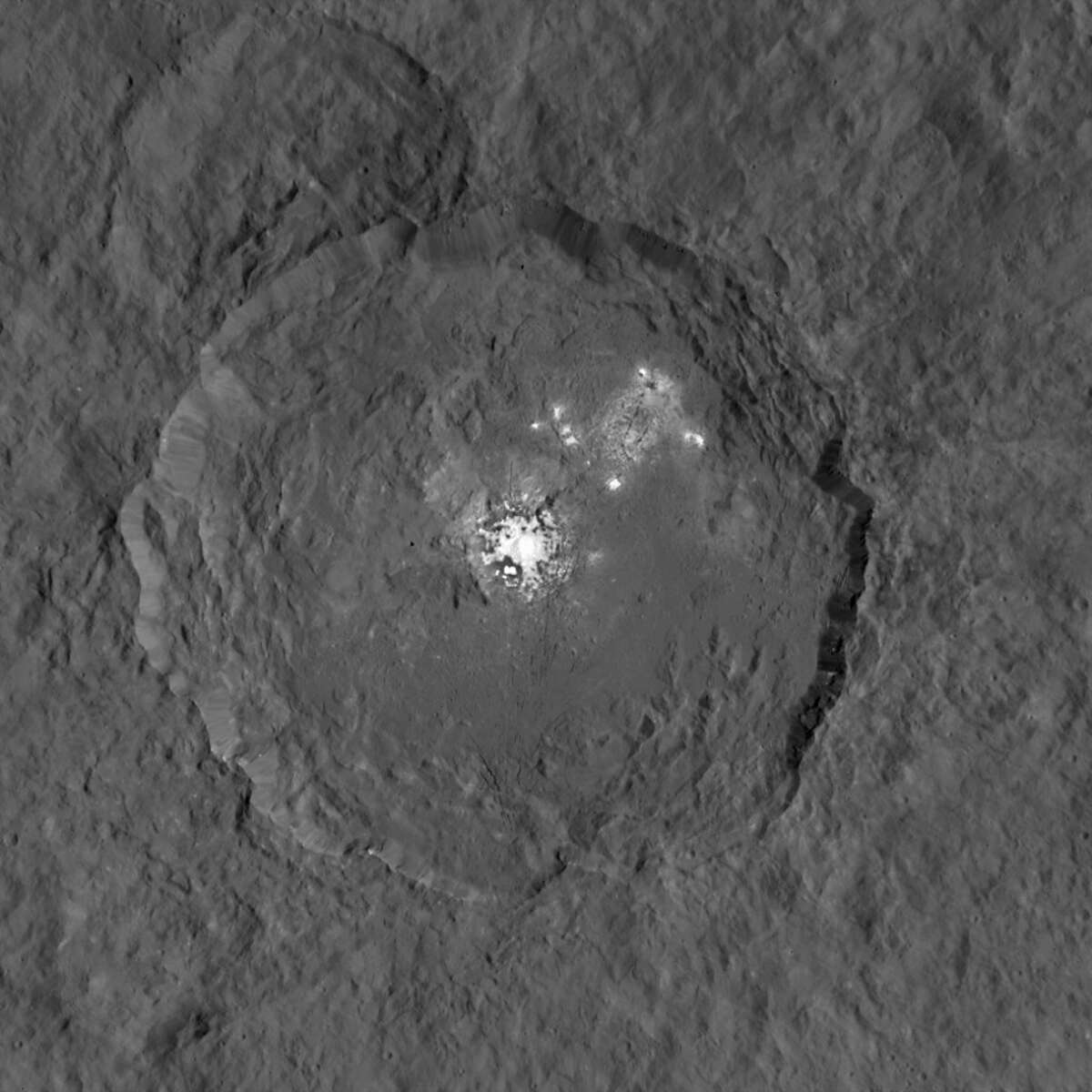 NASA caption: This image, made using images taken by NASA's Dawn spacecraft, shows Occator crater on Ceres, home to a collection of intriguing bright spots. The bright spots are much brighter than the rest of Ceres' surface, and tend to appear overexposed in most images. This view is a composite of two images of Occator: one using a short exposure that captures the detail in the bright spots, and one where the background surface is captured at normal exposure. Image credit: NASA/JPL-Caltech/UCLA/MPS/DLR/IDA