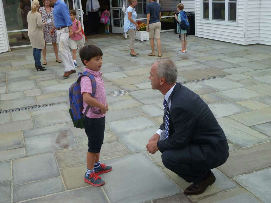 New Canaan Country School Head of School Dr. Robert P. Macrae greets student Jack Engel back on the first day of school on Wednesday. Photo: Martin Cassidy / Hearst Connecticut Media / New Canaan News