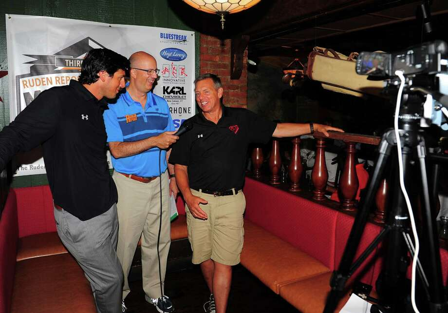 Dave Ruden, center, interviews father and son; New Canaan Head Coach Lou Marinelli and Greenwich Head Coach John Marinelli, left, during the 3rd Annual Ruden Report FCIAC Footbal Media Day held at Bogey's Grill & Tap Room in Norwalk, Conn. on Tuesday Sept. 8, 2015. Photo: Christian Abraham / Hearst Connecticut Media / Connecticut Post