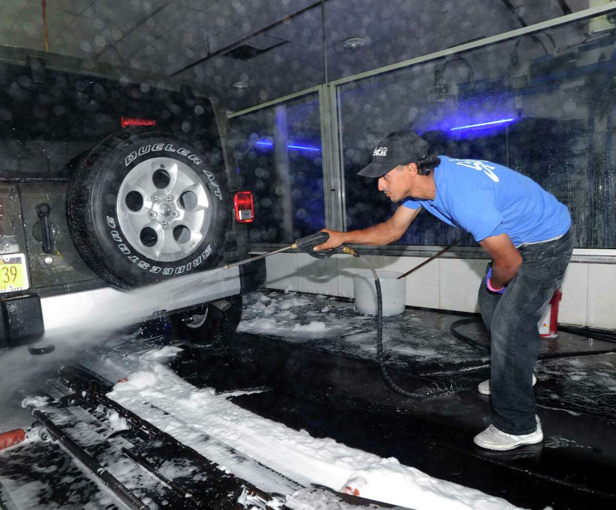 Splash Car Wash worker Mohamed Omar Mohsin sprays down a car at the car wash located at 625 W. Putnam Ave. in Greenwich, Conn., Wednesday, July 22, 2015.