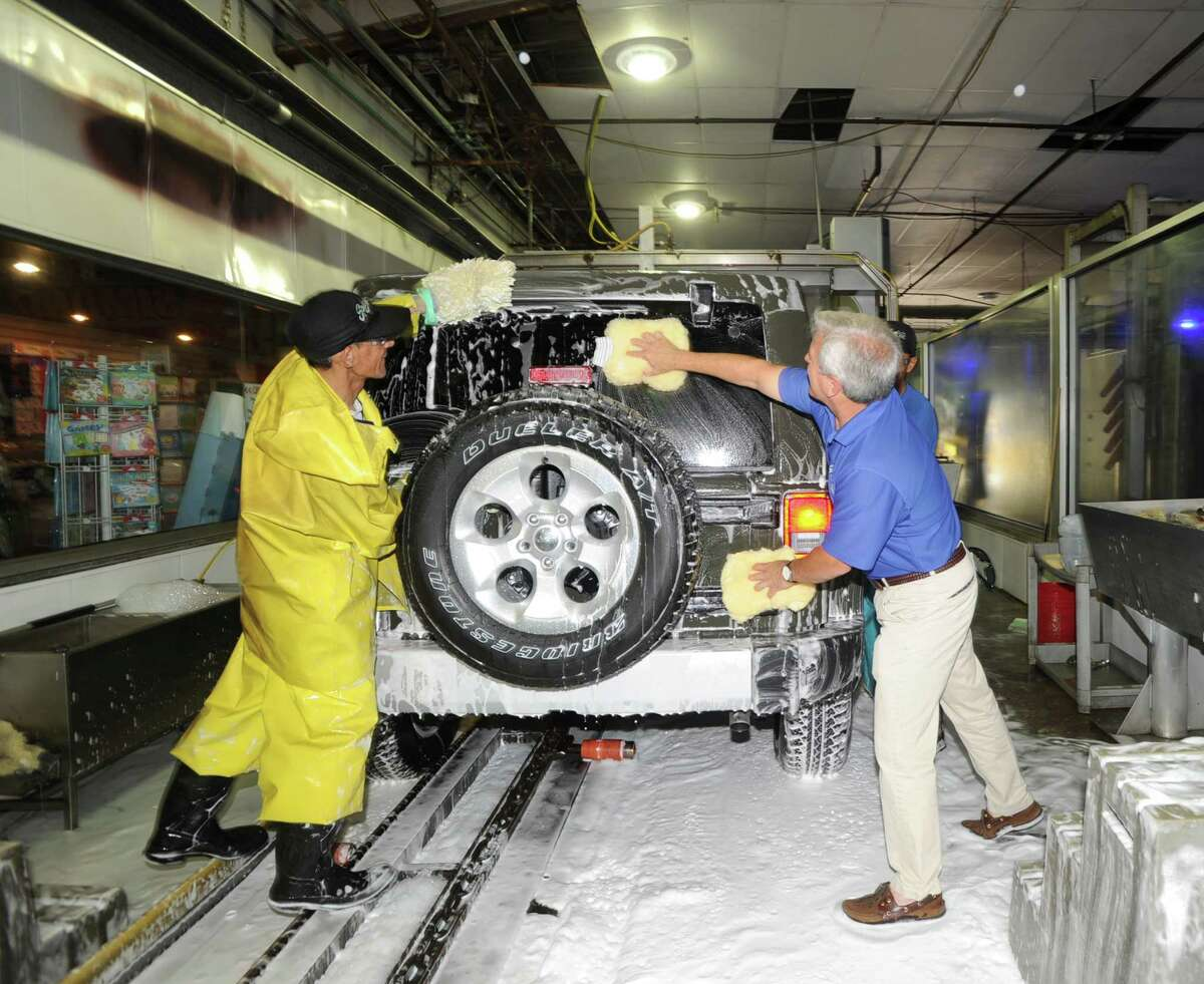 Splash Car Wash owner Mark Curtis, right, works at his car wash at 625 W. Putnam Ave. in Greenwich, Conn., Wednesday, July 22, 2015.