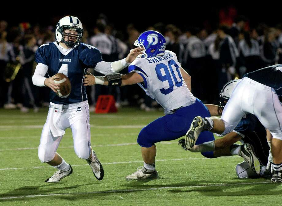 Darien's Mark Evanchick chases Wilton's Rocco Romeo during a game last year. Evanchick, a Hearst Connecticut Media Super 33 All-Star, has the state sack record in his sights. Photo: Lindsay Perry / Hearst Connecticut Media / Stamford Advocate