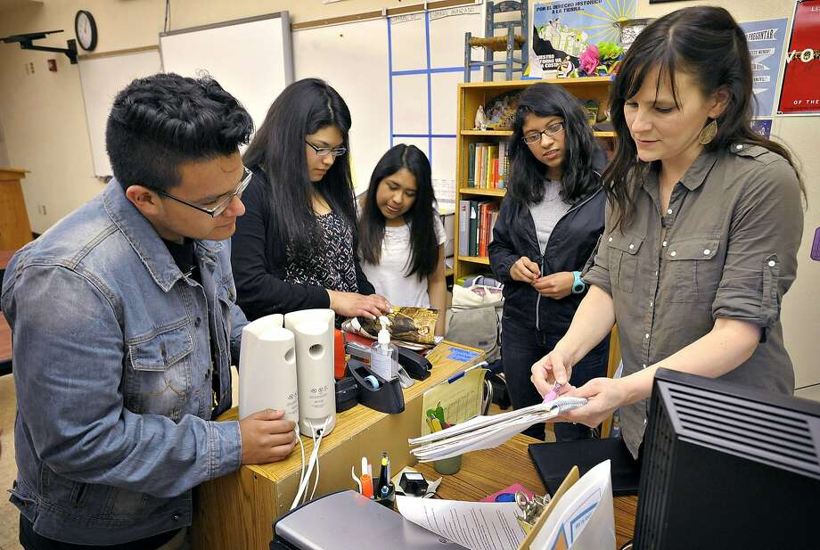 photo might stress that they've done it in oregon.....FILE - This May 28, 2014, file photo shows teacher Amanda Filloy Sharp, right, reviewing potluck items with her students, from left Diego Munoz, Stephanie Vidrio, Thania Lopez and Cynthia Cruz, at the end of class in Corvallis, Ore. Students at Corvallis who have successfully completed dual English and Spanish immersion classes will have an added distinction on their diplomas when they graduate this year, an embossed seal certifying that he or she is bilingual. The honor is part of a pilot project led by several school districts in the state with dual-language programs, and the Oregon Department of Education plans to make the bilingual seals available statewide next year. (AP Photo/The Gazette-Times, Andy Cripe) Photo: Andy Cripe, Associated Press
