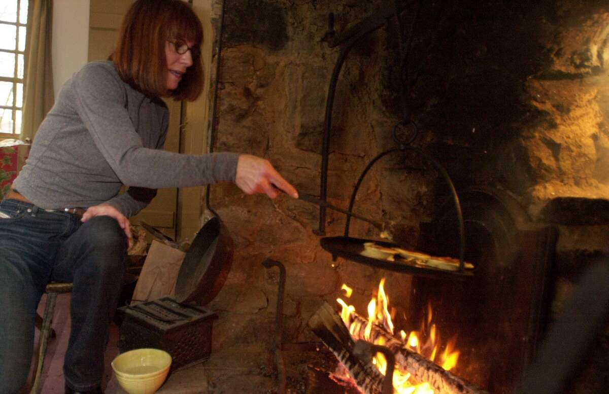 Charlotte Ferguson, an open hearth cooking teacher, demonstrates her hearth cooking techniques.