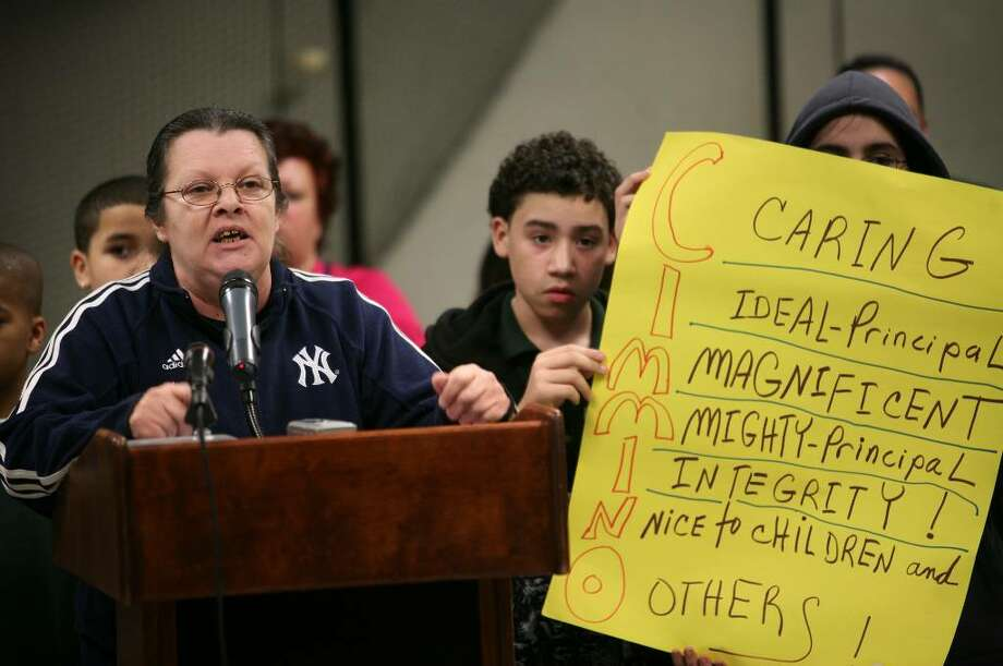 Robin Mastro of Bridgeport addresses the Board of Education in support of Thomas Hooker School principal Andrew Cimmino, on paid leave since September, as Hooker students Edgar Feliciano, 12, and Monet Monterroso hold up a sign, at the Bridgeport Board of Education meeting at the Aquaculture School on Monday, March 22, 2010. Photo: Brian A. Pounds / Connecticut Post