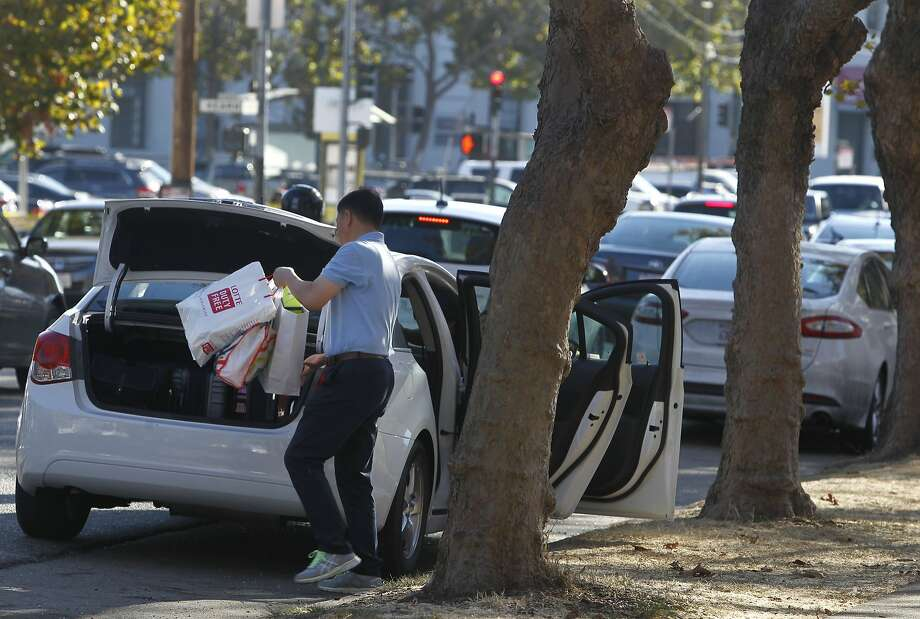 An out-of-town visitor transfers shopping bags to the trunk of a rental car after parking on Bay Street near Kearny Street in San Francisco, Calif. on Wednesday, Sept. 9, 2015. Police officials say auto burglaries have doubled from last year, especially along Bay Street in Fisherman's Wharf, Union Square and the Embarcadero. Photo: Paul Chinn, The Chronicle