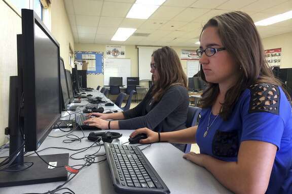 FILE - In this April 30, 2015, file photo, students Leticia Fonseca,16, left, and her twin sister, Sylvia Fonseca, right, work in the computer lab at Cuyama Valley High School after taking the new Common Core-aligned standardized tests, in New Cuyama, Calif. Less than half of all California students passed new math and English tests aligned with the Common Core standards and considered indicators of college and career readiness. Results for the Smarter Balanced assessment released Wednesday, Sept. 9, 2015, show 44 percent of students who took the tests met or exceeded the new language-arts standards. Thirty-four percent passed the assessment in math.  (AP Photo/Christine Armario, File)