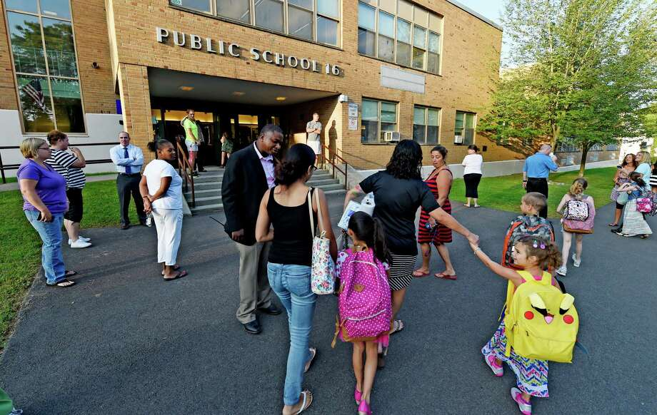 Principal Tracy Ford, sport coat, greets students Wednesday morning Sept. 9, 2015, as they arrive for opening day at Public School 16 in Troy, N.Y.   (Skip Dickstein/Times Union) Photo: SKIP DICKSTEIN / 00033267A