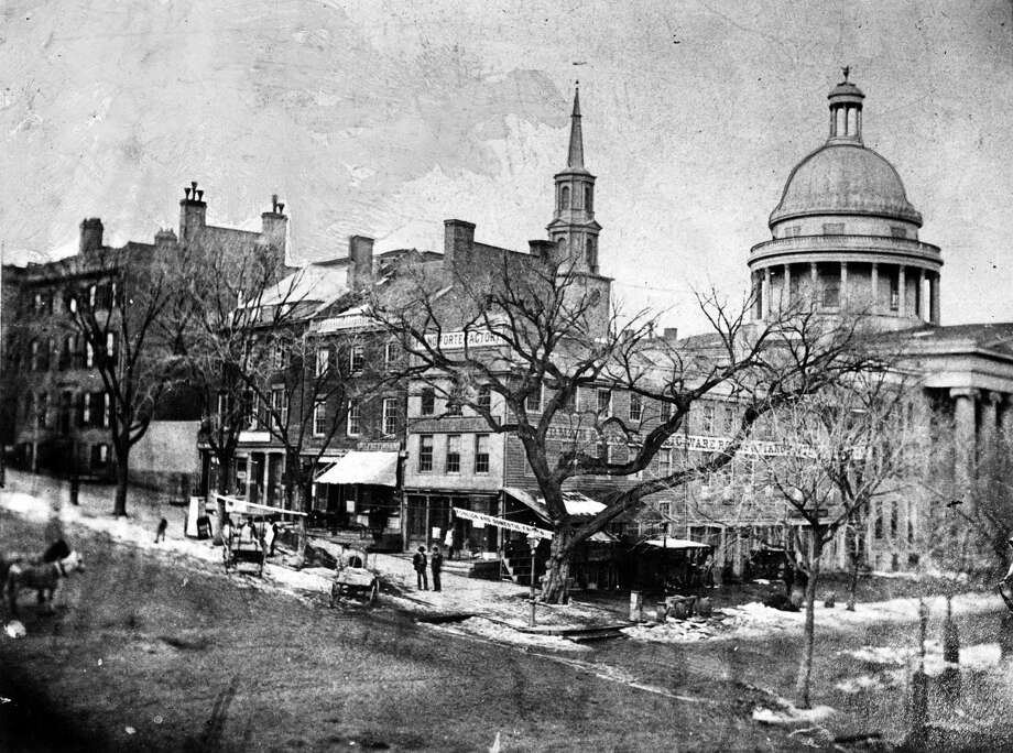 "Historic Albany - Corner of State and North Pearl streets, circa 1865. This was known as ""Elm Tree Corner"" because one of the trees was planted by Philip Livingston (one of the signers of the Declaration of Independence) in 1735. The tree was cut down in 1885 during repaving. The building at the extreme left was the residence of John Young, governor of New York from 1847 to 1849. The original state Capitol building can be seen to the right. (Times Union archive)"