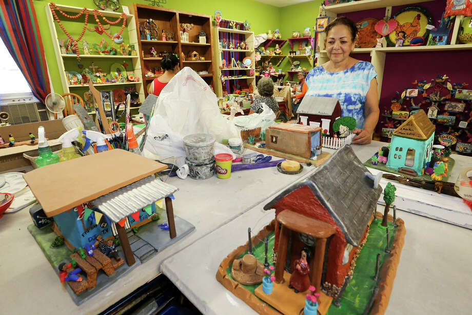 """Imelda Arismendz, coordinator at MujerArtes, looks over clay houses prepared for the West Side copperative's 20th anniversary exhibit and sale, """"Barrio de Barro."""" on Thursday, Sept. 3, 2015.  The exhibit, which opens on Saturday, Sept. 12 at the Esperanza Peace & Justice Center, 922 San Pedro Ave, features local houses, churches and businesses made from clay.  MARVIN PFEIFFER/ mpfeiffer@express-news.net Photo: Marvin Pfeiffer, Staff / San Antonio Express-News / Express-News 2015"""
