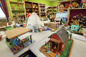 """Imelda Arismendz, coordinator at MujerArtes, looks over clay houses prepared for the West Side copperative's 20th anniversary exhibit and sale, """"Barrio de Barro."""" on Thursday, Sept. 3, 2015.  The exhibit, which opens on Saturday, Sept. 12 at the Esperanza Peace & Justice Center, 922 San Pedro Ave, features local houses, churches and businesses made from clay.  MARVIN PFEIFFER/ mpfeiffer@express-news.net"""