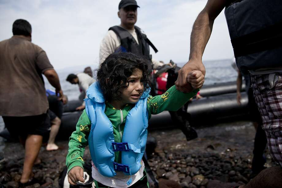 A migrant girl is helped ashore on the Greek island Lesbos. Photo: Petros Giannakouris, Associated Press