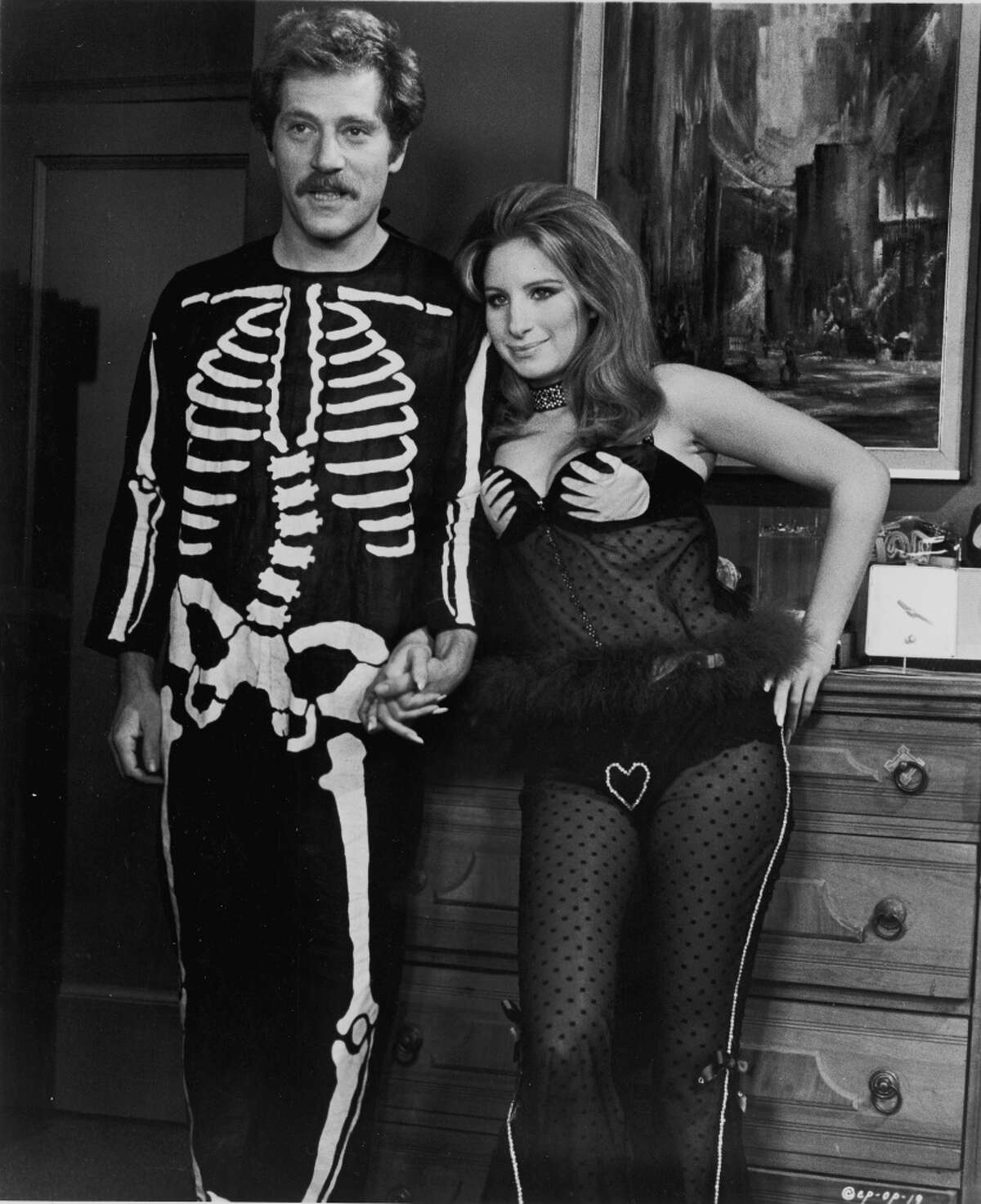 1970: American actors George Segal and Barbra Streisand hold hands, wearing Halloween costumes, in a still from the film, 'The Owl And The Pussycat,' directed by Herbert Ross, 1970.