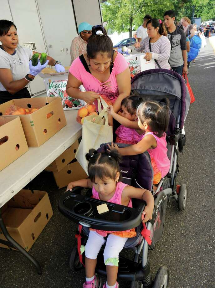 Aida Logano of Danbury brought her triplet daughters with her to the food bank at the New Hope Baptist Church Wednesday, Sept. 9, 2015. The New Hope Baptist Church in conjunction with the Connecticut Food Bank offers fresh produce without charge the second Wednesday of every month from a truck brought to the Danbury church. About 350 families are served by this mobile food bank. Photo: Carol Kaliff / Hearst Connecticut Media / The News-Times