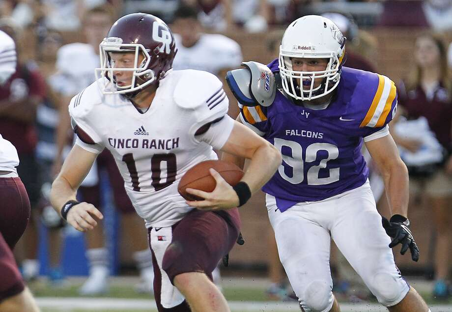 Cinco Ranch quarterback Russell Morrison tries to get away from Jersey Village's Grayson Newton on a quarterback keeper as the two teams faced off at Rhodes Stadium in Katy last week. Cinco Ranch won in the final seconds, 30-27. Photo: Diana L. Porter, Freelance / © Diana L. Porter