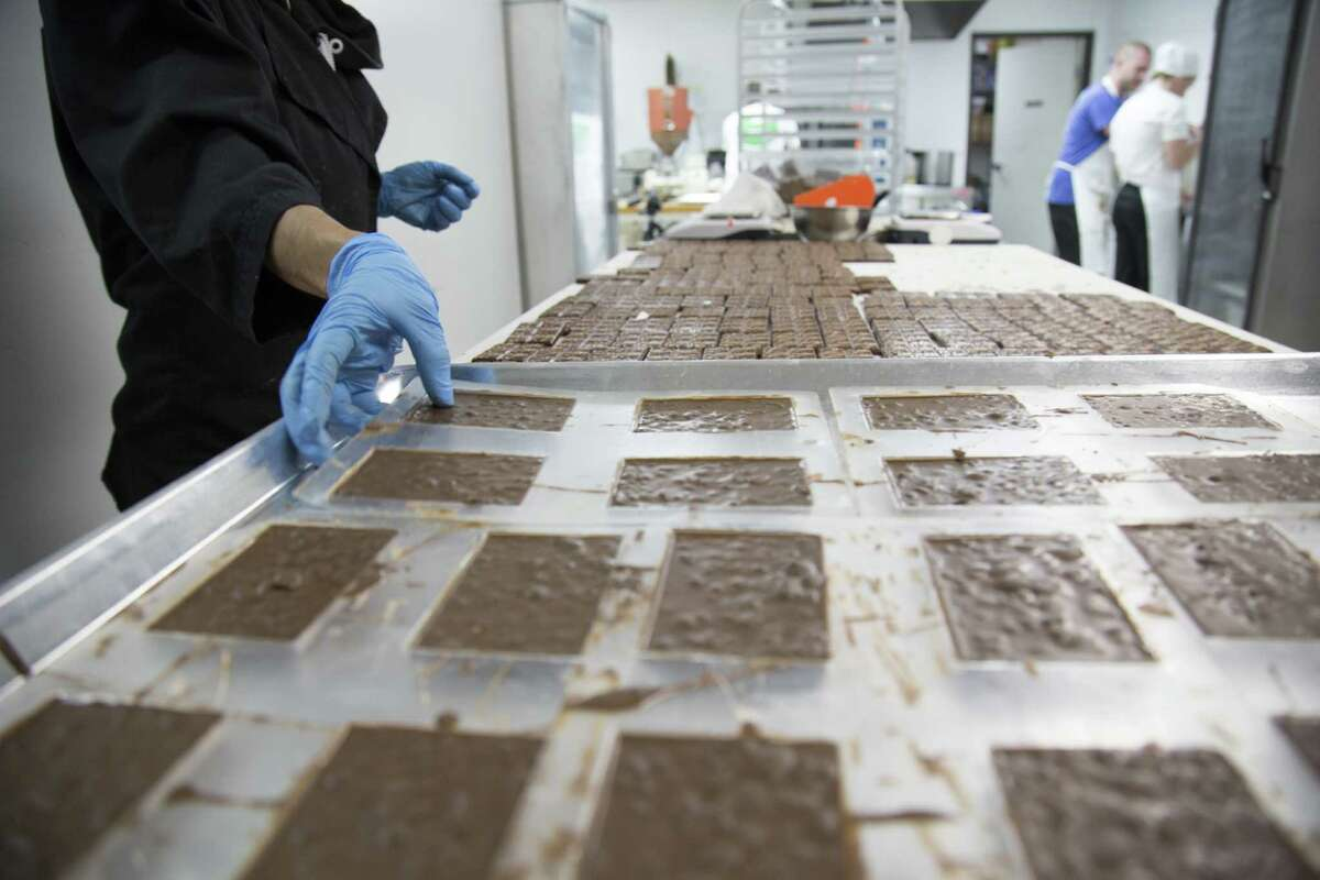 Crystal Atencio of Incredibles grabs a plate of baked chocolate bars infused with marijuana and knocks it from its mold, preparing it to be packaged and labeled.