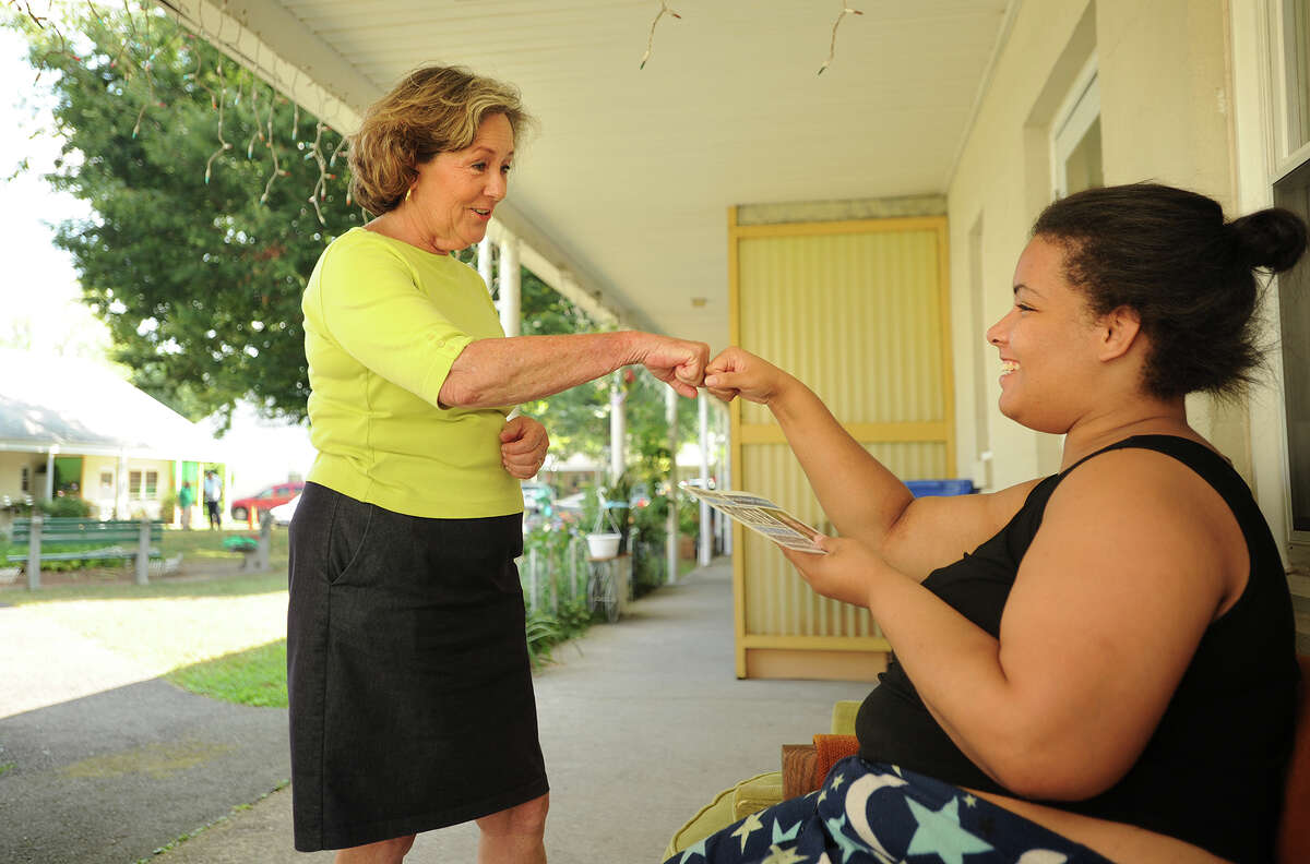 Bridgeport mayoral candidate Mary-Jane Foster, left, gets a fist bump from resident Leslie Santiago as she goes door to door campaigning at Fireside Apartments on Palisade Avenue in Bridgeport, Conn. on Tuesday, September 1, 2015.
