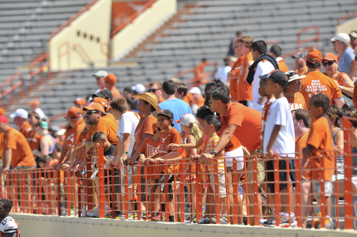 Longhorns football fans line the rail to watch a free, open-to-the-public practice at Royal-Memorial Stadium in Austin in 2013.