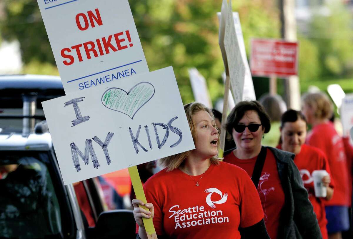 Teachers at West Seattle Elementary School begin walking a picket line Wednesday morning, Sept. 9, 2015, in Seattle after last-minute negotiations over wages and other issues failed to avert a strike in Washington state's largest school district. Classes for 53,000 Seattle Public Schools students were canceled Wednesday, on the scheduled first day of school. (AP Photo/Elaine Thompson)