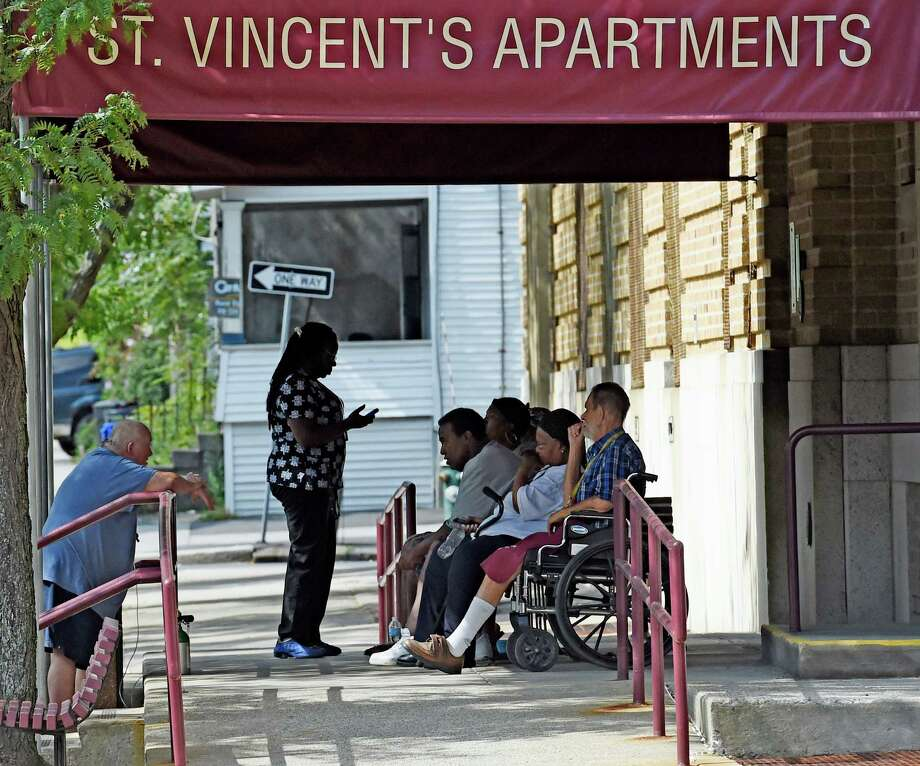 Residents of St. Vincent's Apartments sit under an awning to stay cool Wednesday afternoon Sept. 9, 2015,  after a power outage affected residents of the apartment house in Albany, N.Y.  Three other apartment complexes were affected with approximately 800 persons directly involved.   (Skip Dickstein/Times Union) Photo: SKIP DICKSTEIN