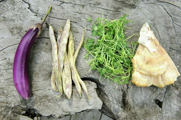 From left are Japanese eggplant, dragon tongue beans, pea shoots and chicken of the woods mushrooms on Saturday, Aug. 29, 2015, in Delmar, N.Y. (Cindy Schultz / Times Union) Photo: Cindy Schultz / 00033132A