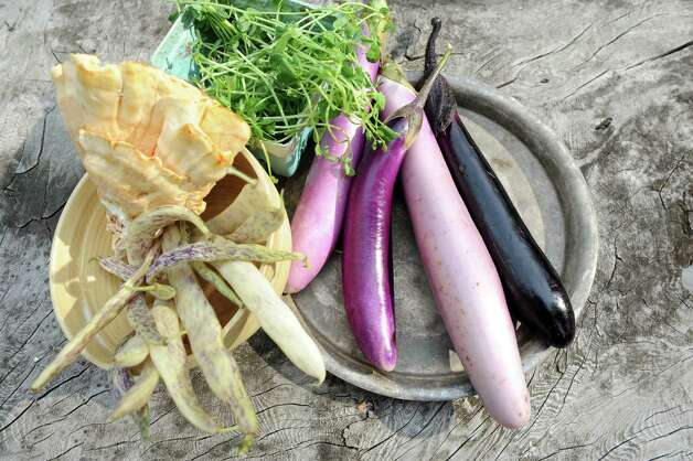 Clockwise from lower left are dragon tongue beans, chicken of the woods mushrooms, pea shoots and Japanese eggplant on Saturday, Aug. 29, 2015, in Delmar, N.Y. (Cindy Schultz / Times Union) Photo: Cindy Schultz / 00033132A