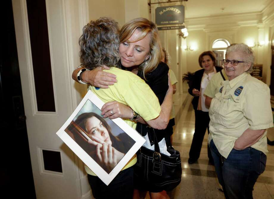 Debbie Ziegler holds a photo of her daughter, Brittany Maynard, as she receives congratulations from Ellen Pontac, after a right-to die measure was approved by the state Assembly, Wednesday, Sept. 9, 2015, in Sacramento, Calif. The bill, approved on a 42-33 vote, that would allow terminally ill patients to legally end their lives, now goes to the Senate.  Brittany Maynard was the California woman with brain cancer who moved to Oregon to legally end her life last fall. (AP Photo/Rich Pedroncelli) Photo: Rich Pedroncelli, STF / AP