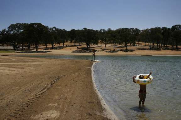 Anthony James Meleen, 3, struggles to get his arms through a floatation device while playing with family in the swimming lagoon at Don Pedro reservoir as it hovers at 32 percent of its total capacity Aug. 19, 2015 in La Grange, Calif.