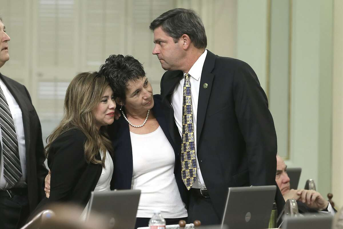 Assemblywoman Susan Talamantes Eggman, D-Stockton, center, is congratulated by Assembly members Nora Campos, D-San Jose and Jim Wood, D-Healdsburg, after her right-to die measure was approved by the state Assembly Wednesday, Sept. 9, 2015, in Sacramento, Calif. The bill, approved on a 42-33 vote, that would allow terminally ill patients to legally end their lives, now goes to the Senate.(AP Photo/Rich Pedroncelli)