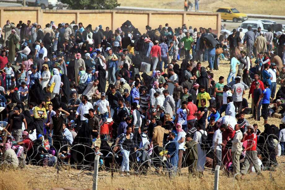 In this photo taken from the Turkish side of the border between Turkey and Syria, in Akcakale, Sanliurfa province, southeastern Turkey,  Syrian refugees wait on the Syrian side of the border in order to cross, Saturday, June 13, 2015.  Turkey's emergency management agency says more than 6,000 Syrians have crossed into Turkey in the past week, fleeing fighting between Islamic State militants and Kurdish forces near the northern Syrian city of Tel Abyad.  (AP Photo/Lefteris Pitarakis) Photo: Lefteris Pitarakis, STF / AP