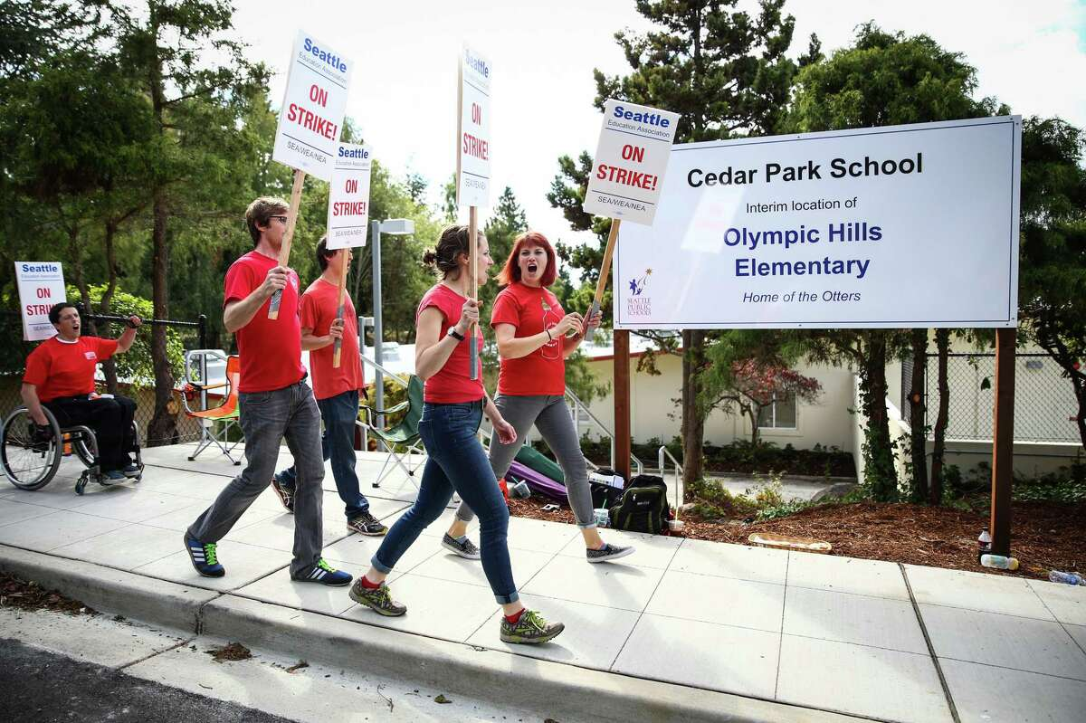 Teachers march outside of Olympic Hills Elementary in the Cedar Park School on what should have been the grand opening of the northeast Seattle school during day one of a strike by Seattle Public School teachers and staff members. Photographed on Wednesday, September 9, 2015.