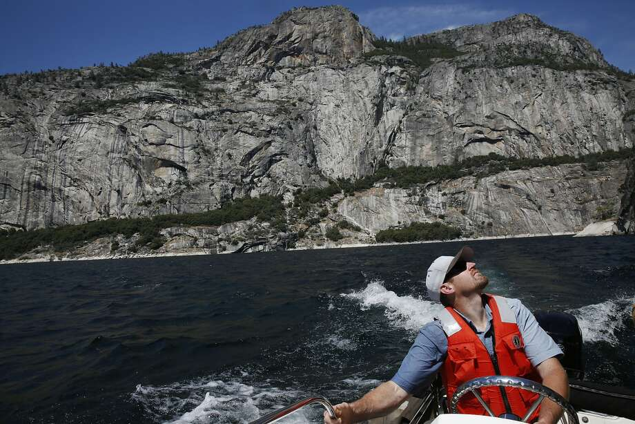 Bob Slater, a dam tender, checks out the sheer granite cliffs above the lake as he pilots a boat for a media tour on Hetch Hetchy Reservoir. Photo: Leah Millis, The Chronicle