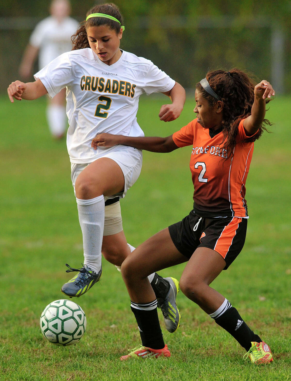 Stamfor's Aolani Hermosura flicks the ball from Trinity Catholic's Christina Bellacicco during their soccer game at Trinity Catholic High School in Stamford, Conn., on Tuesday, Oct. 21, 2014. Stamford won, 5-0.