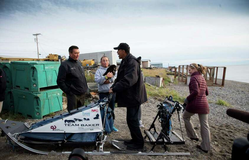 President Barack Obama stands on a dog sled as he talks with John Baker, left, the 2011 Iditarod Dog