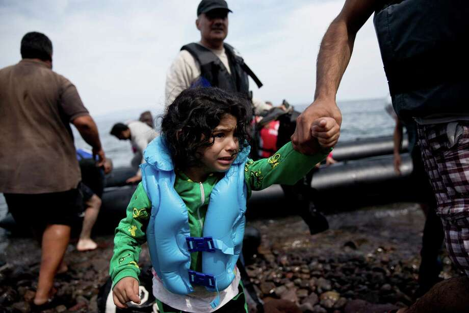 A young migrant is helped ashore as she arrives aboard a dinghy after crossing from Turkey to Lesbos island, Greece. The EU's top official is asking Europe to face up to its immigration crisis. Photo: Petros Giannakouris /Associated Press / AP