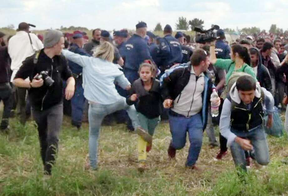 This video grab released Wednesday shows a Hungarian TV camerawoman kicking a child as she run with other migrants from a police line during disturbances at Roszke, southern Hungary. After the footage appeared, the camerawomen was fired by N1TV, an internet-based TV station.  Photo: -, Staff / AFP